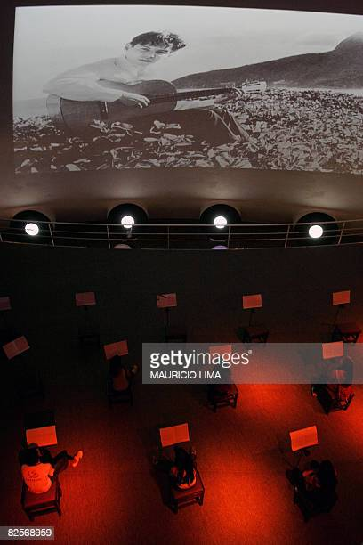 Visitors take part in an interactive showing as part of an exhibition to celebrate the 50th anniversary of Brazilian movement and musical style...