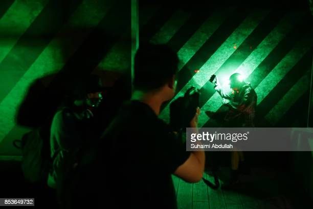 Visitors take part in the allnew zombie laser tag experience during Halloween Horror Nights 7 Media Preview on September 25 2017 in Singapore From 29...