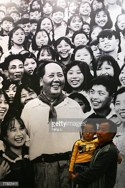Visitors take photo in front of a billboard showing picture of Chinese leader Mao Zedong on display ahead of the 17th Communist Party Congress at...