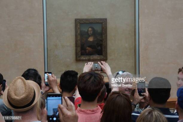 Visitors take photo in front of Leonardo da Vinci's Mona Lisa painting at the Louvre Museum in Paris France June2019 Photo by Mikhail Svetlov/Getty...