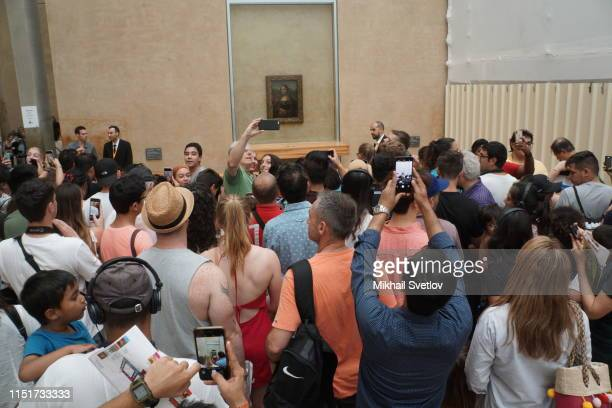Visitors take photo in front of Leonardo da Vinci's Mona Lisa painting at the Louvre Museum in Paris France June2019 Photo by Mikhail Svetlov/Getty...