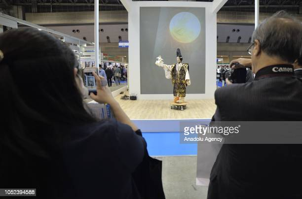 Visitors take photo of a THK Co's SeedNoid robot performing a Noh musical drama at the Japan Robot Week 2018 at Tokyo Big Sight Japan on October 17...