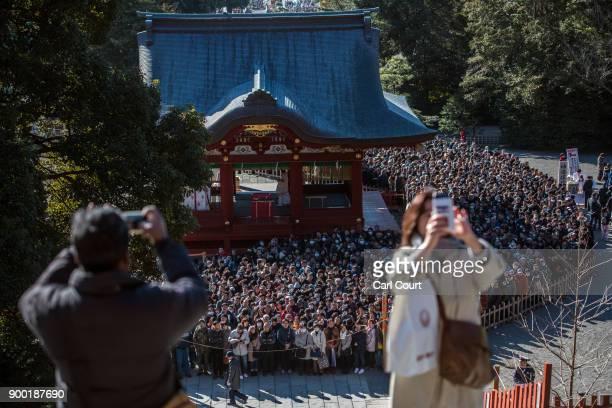 Visitors take photographs as others queue to pray for the new year at Tsurugaoka Hachimangu Shinto shrine on January 1 2018 in Kamakura Japan...