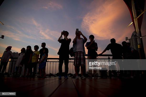 Visitors take photographs at Asiatique The Riverfront openair mall at dusk in Bangkok Thailand on Friday Dec 18 2015 Thai economic indicators have...