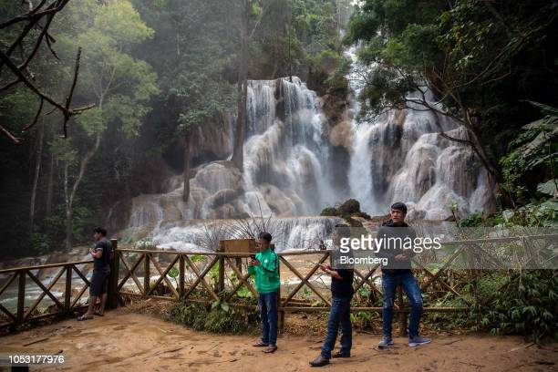 Visitors take photographs at the Kuang Si Waterfall in Luang Prabang Province Laos on Sunday Oct 21 2018 Laos's economy is set to expand at 7 percent...