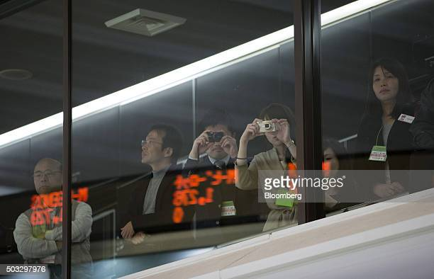 Visitors take photographs at the Tokyo Stock Exchange operated by Japan Exchange Group Inc on the first trading day of the year in Tokyo Japan Monday...