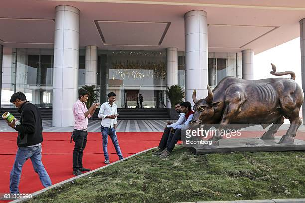 Visitors take photographs in front of a bull statue at the India International Exchange building operated by India International Clearing Corp a...