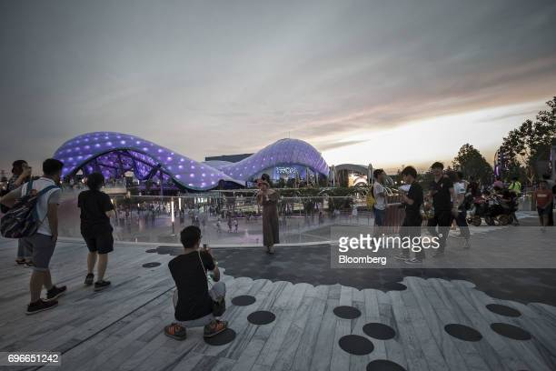 Visitors take photographs in front of the TRON Lightcycle Power Run roller coaster attraction during the oneyear celebration of Walt Disney Co...