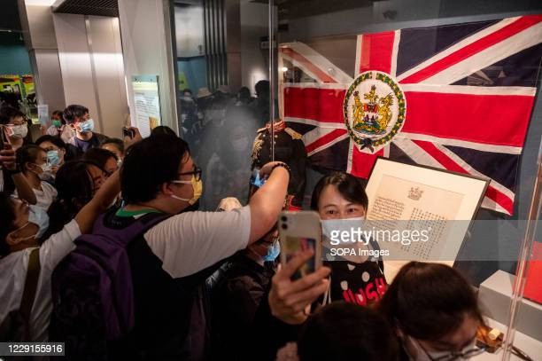 Visitors take photographs of a colonial British Hong Kong flag at the Hong Kong museum of History. The permanent exhibition of the museum will close...