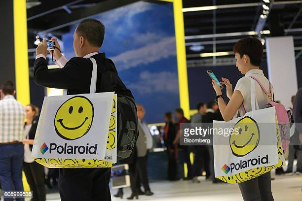Visitors take photographs of trade stands whilst holding Polaroid branded bags during the Photokina photography trade fair in Cologne Germany on...