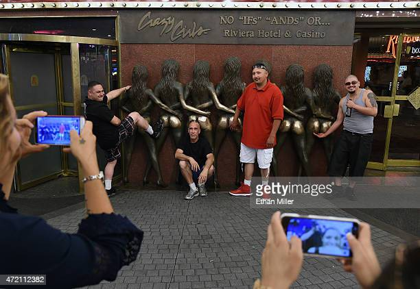 Visitors take photos at the Crazy Girls bronze sculpture at the Riviera Hotel Casino on its last day of operation on May 3 2015 in Las Vegas Nevada...