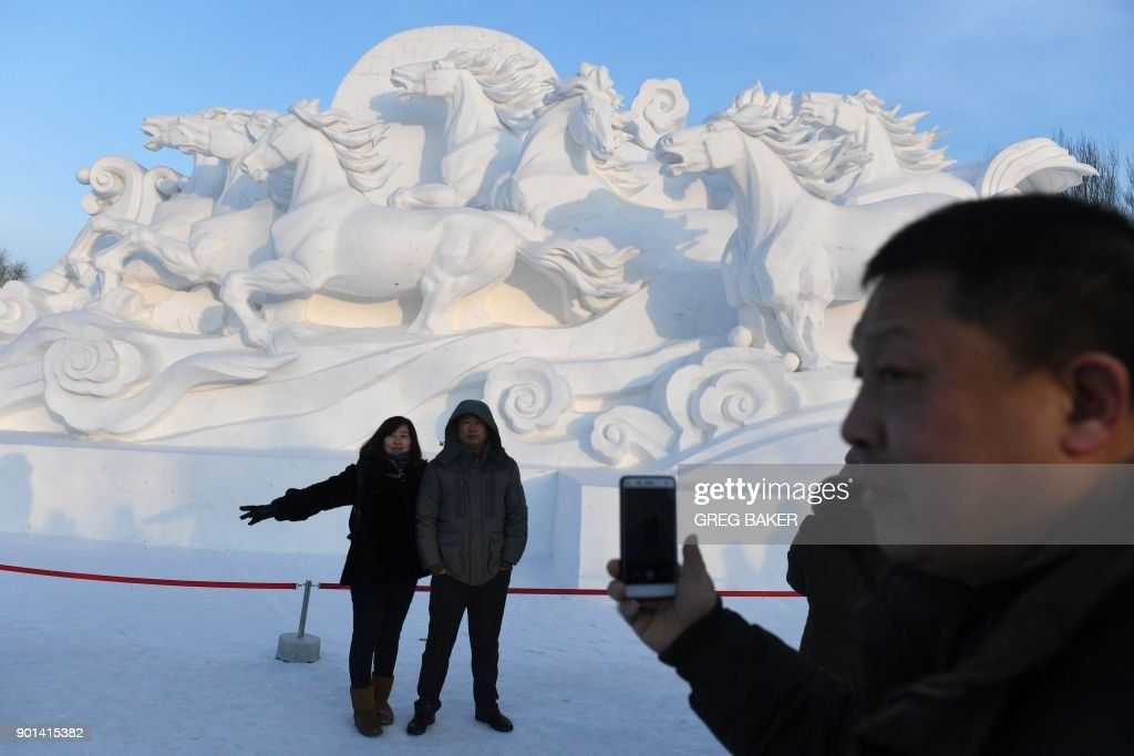 Visitors take photos in front of a snow sculpture before the opening of the annual Harbin Ice and Snow Sculpture Festival in Harbin in China's northeast Heilongjiang province on January 5, 2018. The festival attracts hundreds of thousands of visitors annually. / AFP PHOTO / Greg Baker