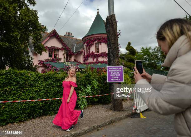 Visitors take photos in front of the house in The Burnaby area of Greystones which has been covered from the roof down by stretched pink flowers and...