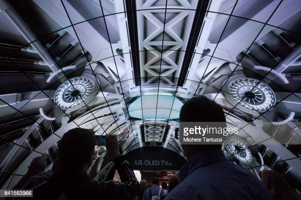 Visitors take photos of a LG Oled TV 4K screen tunnel at the LG stand at the 2017 IFA consumer electronics and home appliances trade fair on...