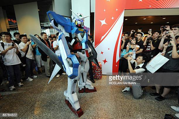Visitors take photos of a lifesize plastic model of Gundam 00 a Japanese cartoon anime character at the Anime Festival Asia exhibition in Singapore...