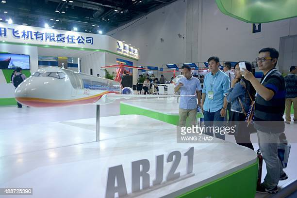 Visitors take photos of a model of the ARJ21 designed by Commercial Aircraft Corporation of China at the Beijing International Aviation Expo in...