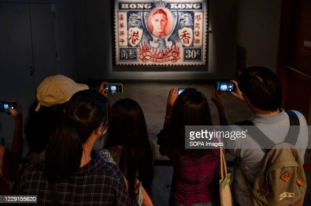 Visitors take photos of a poster of a British Hong Kong stamp featuring a portrait of King George VI at the Hong Kong museum of History. The...