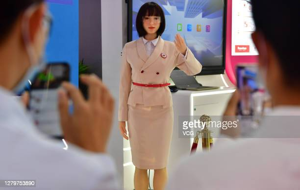 Visitors take photos of an AI humanoid education robot developed by NetDragon Websoft Inc. During the 3rd Digital China Summit & Exhibition at the...