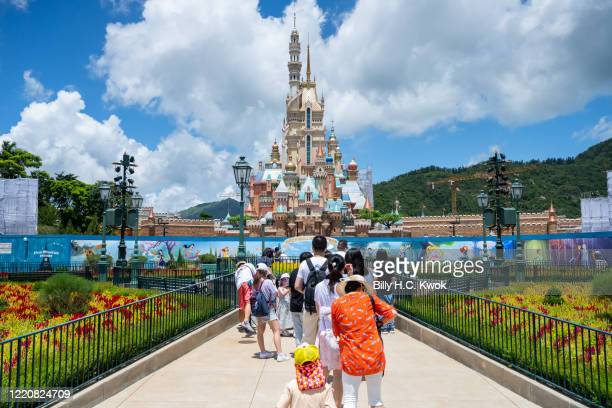 Visitors take photos of the Castle of Magical Dreams in Walt Disney Co's Disneyland Resort on June 18 2020 in Hong Kong China