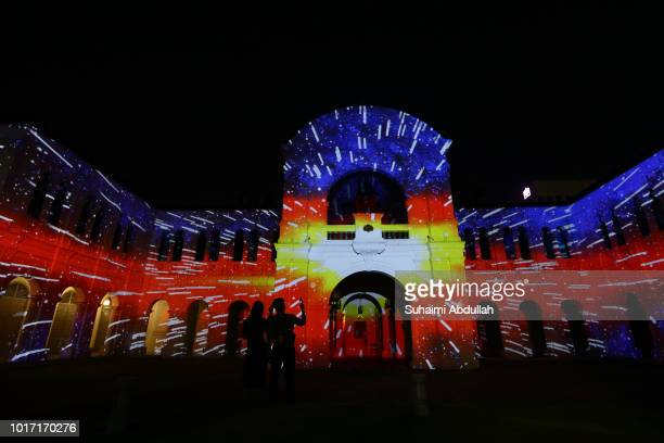 Visitors take photos of the projection mapping installation on the facade of the Singapore Art Museum titled Odyssey by Arnaud Pottier and Thimothee...