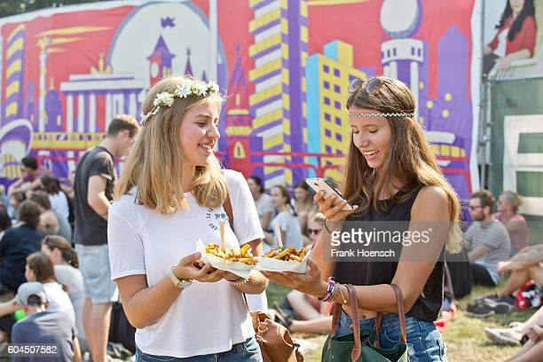 Visitors take photos of their food during the second day of Lollapalooza Festival at the Treptower Park on September 11 2016 in Berlin Germany