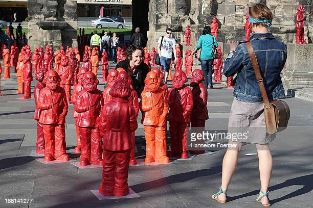 Visitors take photos with some of the 500 one meter tall statues of German political thinker Karl Marx on display on May 5 2013 in Trier Germany The...