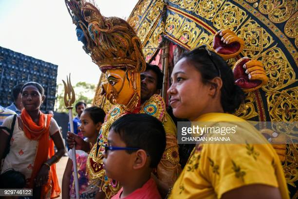 Visitors take picture with Indian artists dressed as goddess Durga during a cultural event in New Delhi on March 9 2018 / AFP PHOTO / CHANDAN KHANNA