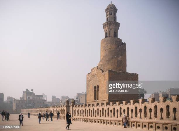 Visitors take pictures as they walk along the roof of the ninth century mosque of Ibn Tulun in the Egyptian capital Cairo on January 11 with the...