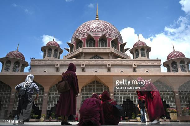 Visitors take pictures in front of the Putra Mosque in Putrajaya on February 21 2019