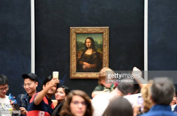Visitors take pictures in frront of Mona Lisa after it was returned at its place at the Louvre Museum in Paris on October 7 2019 Leonardo da Vinci's...