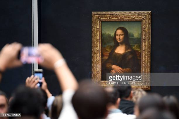 TOPSHOT Visitors take pictures in frront of Mona Lisa after it was returned at its place at the Louvre Museum in Paris on October 7 2019 Leonardo da...