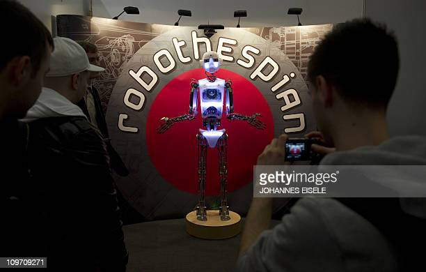 Visitors take pictures of a lifesized humanoid robot named 'RoboThespian' created to educate communicate interact and entertain at the CeBIT IT fair...