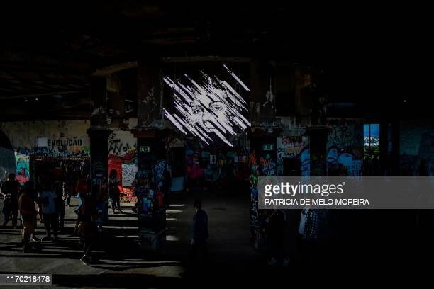 Visitors take pictures of an artwork by Portuguese artist Vhils at the Monsanto panoramic viewpoint during the Iminente Festival in Lisbon on...