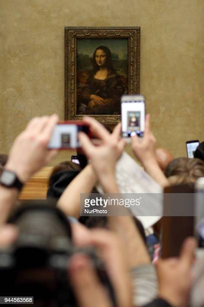 Visitors take pictures of 'La Joconde' a 15031506 oil on wood portrait of Mona Lisa by Leonardo Da Vinci at the Louvre Museum in Paris on April 9 2018