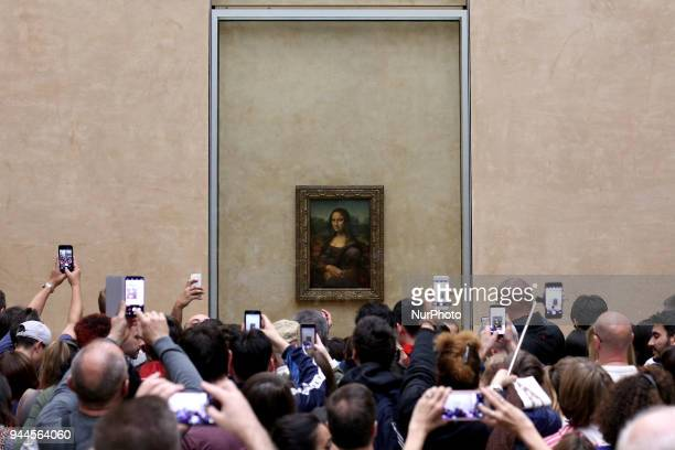 Visitors take pictures of 'La Joconde', a 1503-1506 oil on wood portrait of Mona Lisa by Leonardo Da Vinci, at the Louvre Museum in Paris, on April...