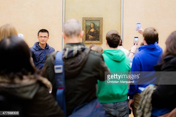 Visitors take pictures of Leonardo da Vinci 'Mona Lisa' inside the Louvre museum on February 28 2014 in Paris France The museum is housed in the...