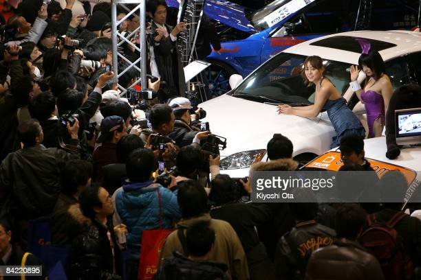 Visitors take pictures of models posed with a customized car displayed at a booth at Tokyo Auto Salon 2009 at Makuhari Messe on January 9 2009 in...