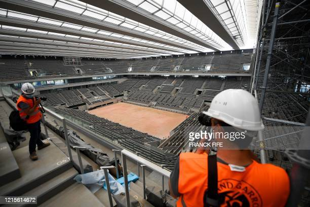 Visitors take pictures of newly built roof of the Philippe Chatrier central tennis court at the Roland Garros stadium in Paris on May 27 2020 The...