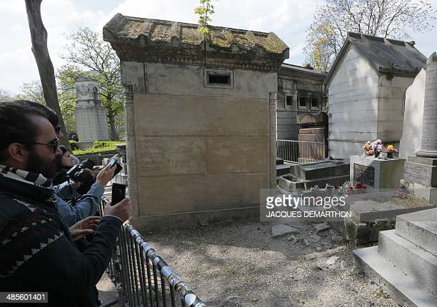 Visitors take pictures of the grave of the leader of the rock group The Doors Jim Morrison on April 19 2014 at the Pere Lachaise cemetery in Paris...