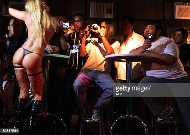 Visitors take pictures on April 19 2008 during a show at the 12th Erotika Fair Latin America's biggest erotica trade show held at the exhibition hall...