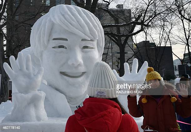 Visitors take pictures with a large snow sculpture of Japan's figure skater Yuzuru Hanyu during the 66th annual Sapporo Snow Festival on February 5...