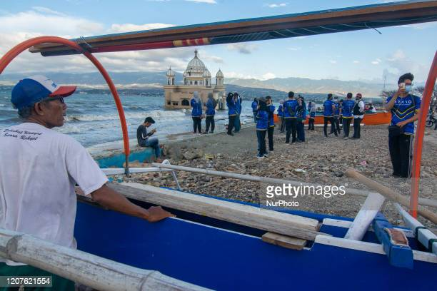 Visitors take pictures with the background of the Floating Mosque that collapsed into the sea due to the tsunami struck at Kampung Lere Beach Palu...