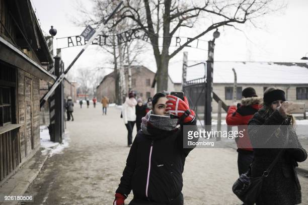 Visitors take 'selfie' photographs near the main gate at the AuscwitzBirkenau concentration camp museum in AuscwitzBirkenau Poland on Wednesday Feb...