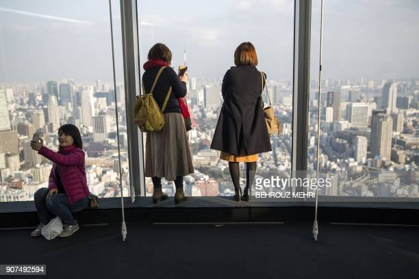 TOPSHOT Visitors take selfies and pictures of the Tokyo skyline from the Roppongi Hills commercial complex on January 20 2018 / AFP PHOTO / Behrouz...