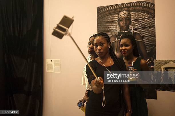 Visitors take selfies during the opening of the Lagos Photo festival in Lagos on October 22, 2016. Lagos Photo was launched in 2010 and is the first...