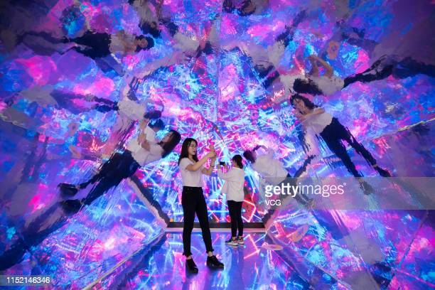 Visitors take selfies in the 'Kaleidoscope' installation at an experience centre on May 27 2019 in Hohhot Inner Mongolia Autonomous Region of China