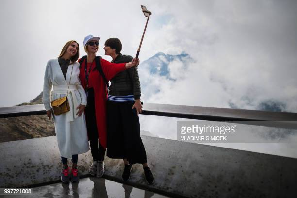 Visitors take selfies on July 11 2018 on the terrace of the James Bond cinematic installation named '007 ELEMENTS' at the top of the Gaislachkogl...
