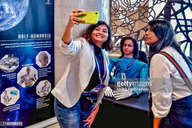 Visitors take selfies with 'Vyommitra' the first prototype half humanoid robot developed by the Inertial Systems Unit of Indian Space Research...