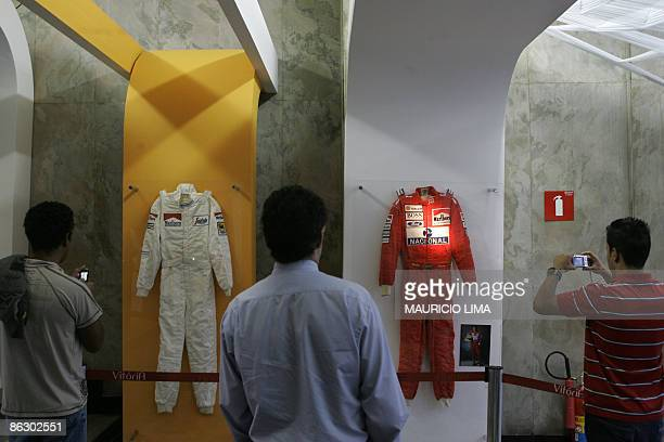 Visitors take snapshots of jackets used by the threetime F1 World Champion late Brazilian Ayrton Senna during the opening of the 'Victory' exhibition...