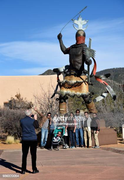 Visitors take souvenir photographs in front of a bronze sculpture depicting an Apache Mountain Spirit Dancer by Craig Dan Goseyun in the plaza of the...